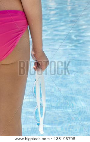 close back view of young Caucasian girl in pink slips standing with blue goggles in hand. Swimming pool in background.