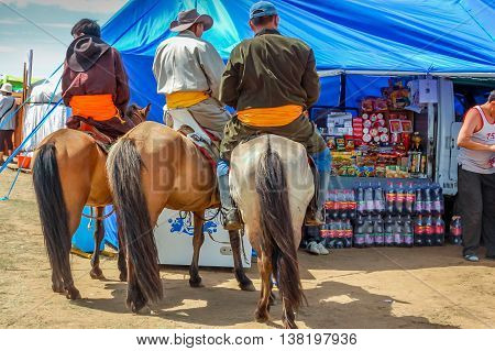 Khui Doloon Khudag Mongolia - July 12 2010: Horseback locals by stall at Nadaam (Mongolia's most important festival whose roots lie in Mongolian warrior traditions) horse race near capital Ulaanbaatar.