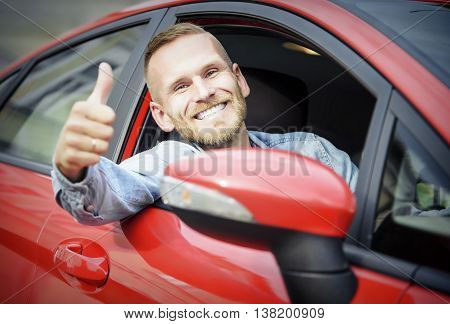 Man at the wheel of his new car, showing thumb up.
