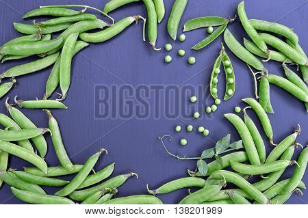 the fresh green sweet peas.top view.raw sugar snap peas.Pods of green peas and pea on a dark background.