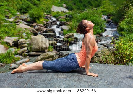 Yoga outdoors  - woman practices Ashtanga Vinyasa yoga Surya Namaskar Sun Salutation asana Urdhva Mukha Svanasana - upward facing dog pose