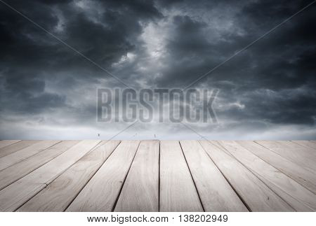 Empty wooden platform and dark stormy sky and stormy sea waves.