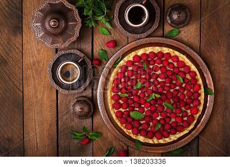 Tart With Raspberries And Whipped Cream Decorated With Mint Leaves On A Wooden Background. Top View