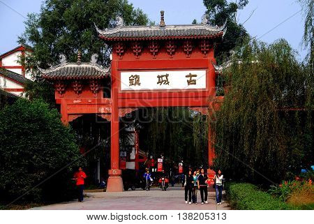 Pixian China - November 10 2007: A large wooden ceremonial entrance gate with flying eaved tiled roofs leads into the town's principle street