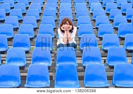 Glum Woman Sitting In Spectator Seating