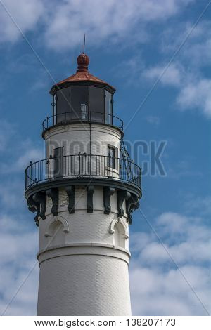 A photograph of a beautiful tall Lake Michigan lighthouse against a pleasant summer sky.