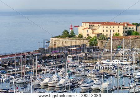 Ajaccio France - May 27 2016: View of the center of capital city of Corsica and birthplace of Napoleon Bonaparte with its marina Fishing Port water front and the lighthouse of the citadel overlooking the bay.