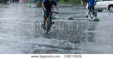 bicycle riders in the rainy city street.