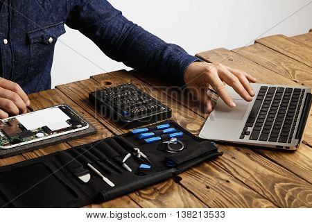 Unrecognizable man uses laptop to find guides how to repair electronic device Tool bag and broken gadget near on vintage wooden table