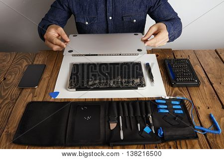 Service man opens backside topcase cover of computer laptop before repairing, cleaning and fixing it with his professional tools from toolkit box near on wooden table front view