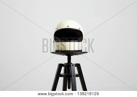 classic motorbike fullface helmet, blank, ivory, isolated on white on black luxury presentation chair, frontside