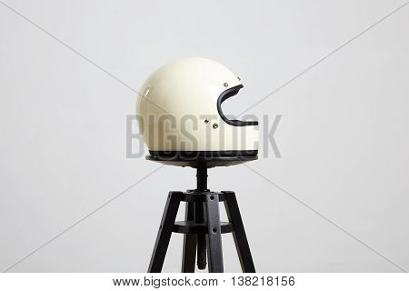 classic motorbike fullface helmet, blank, ivory, isolated on white on black luxury presentation chair, right side