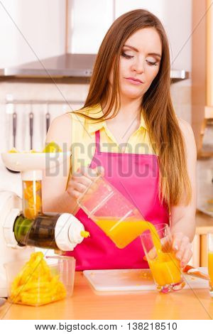 Woman Make Orange Juice In Juicer Machine Pouring Drink In Glass
