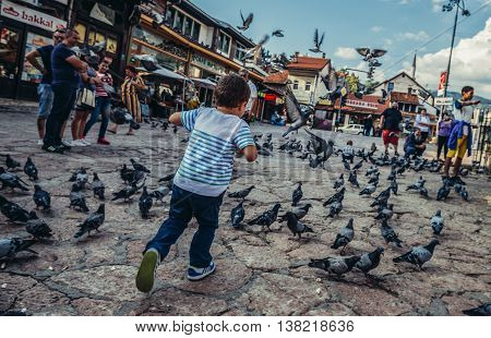 Sarajevo Bosnia and Herzegovina - August 23 2015. Boy chases doves at old bazaar and the historical and cultural center of the Sarajevo called Bascarsija