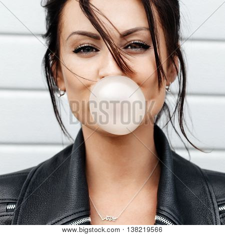Beautiful Young Woman Blowing A Bubble Gum Balloon