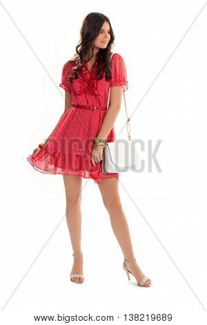 Woman in red v-neck dress. White bag and bead necklace. Elegant and beautiful. Model of fashion magazine.