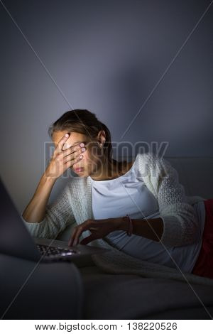 Very tired young woman, burning the midnigh oil - working late at night on her laptop computer, at home, sitting on sofa, rubbing her tired eyes, trying to stay focused