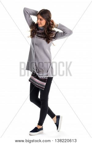 Lady in gray sweater. Pullover and bag with print. Skinny pants and slip ons. Young model wears spring outfit.