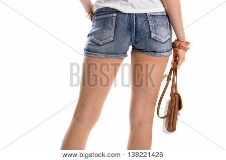 Woman's hand holds brown bag. Back view of denim shorts. Trendy handbag and bracelets. Set of new accessories.