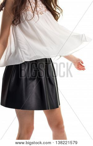 Woman in short black skirt. Blouse in the wind. Garment made of light material. Cotton top and leather skirt.