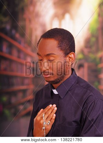 Catholic priest wearing traditional clerical collar shirt standing performing sign of the cross and holding rosary in hand, religion concept.