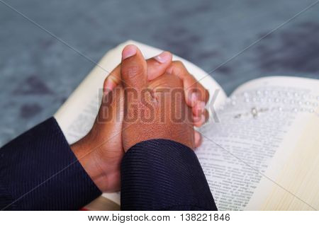 Man folding hands praying with open bible lying in front, seen from behind models head, religion concept.