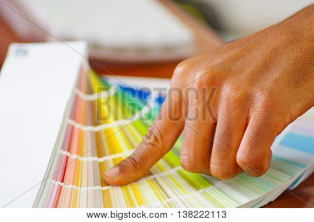 Closeup hands holding palette, colormap spread out in front of white computer keyboard, designer concept.
