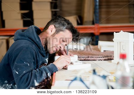 Man Engraving A Plaster Model Building
