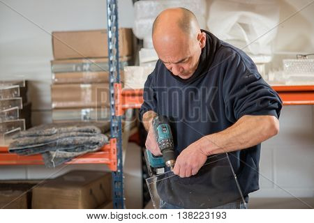 Man Drilling A Clear Acrylic Frame