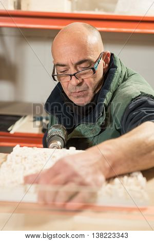 Man Perforating A Plaster Model With Electric Drill
