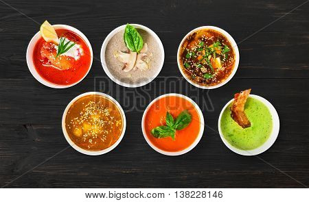 Variety of restaurant hot dishes, healthy food. Japanese miso soup, asian fish soup, russian borscht, english pea soup with bacon, mushroom soup, spanish gazpacho at black rustic wood, top view