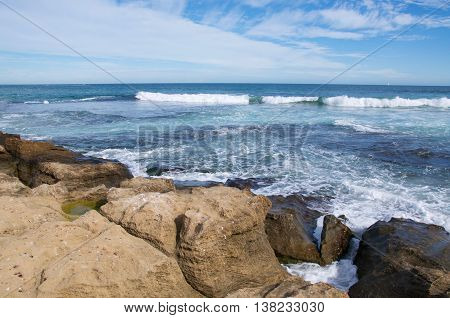 Scenic Indian Ocean view with foamy waves and limestone rock formations under a blue sky with clouds at Penguin Island in Rockingham, Western Australia.