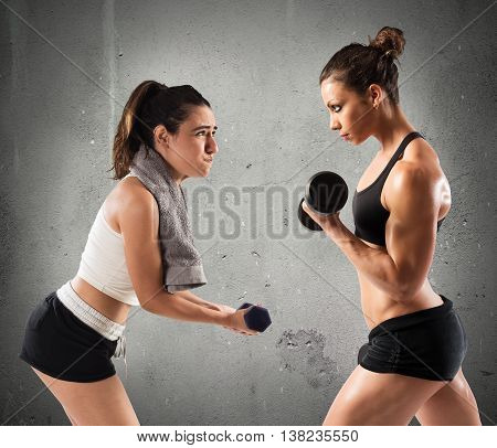 Muscular girl trains with a clumsy girl