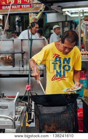GEORGE TOWN MALAYSIA - MARCH 22: Senior man cooks kway teow noodles in asian wok at the Kimberly Street Food Night Market on March 22 2016 in George Town Penang Malaysia.