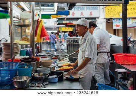 GEORGE TOWN MALAYSIA - MARCH 22: Senior man sells noodles at the Kimberly Street Food Night Market on March 22 2016 in George Town Penang Malaysia.