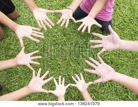 Children hands on green grass background, spring time.