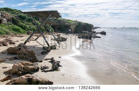 Penguin Island beach with wooden shelter, limestone caves and calm Indian Ocean waters under an overcast sky in Rockingham, Western Australia. poster