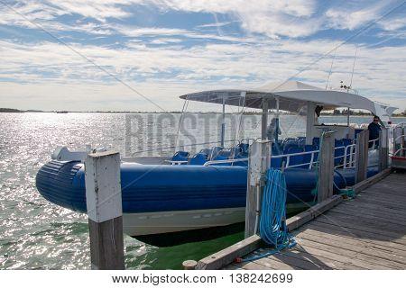 ROCKINGHAM,WA,AUSTRALIA-JUNE 3,2016: Rockingham Wild Encounters cruise boat  docked at Penguin Island in the Indian Ocean under a cloudy sky in Rockingham, Western Australia.