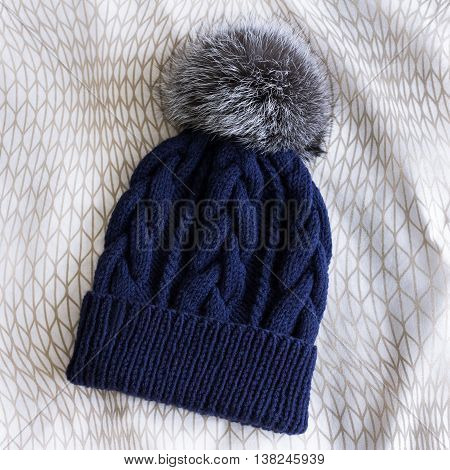 blue knitted cap with silver foxfur pompom