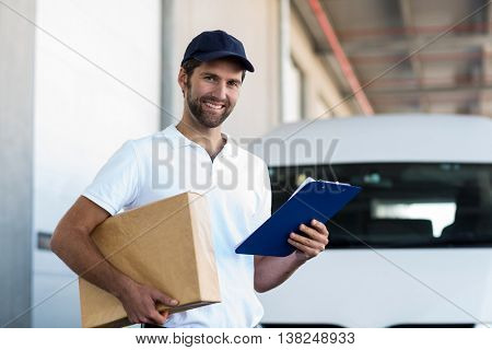 Delivery man is holding a cardboard box and a clipboard and posing in front of a warehouse