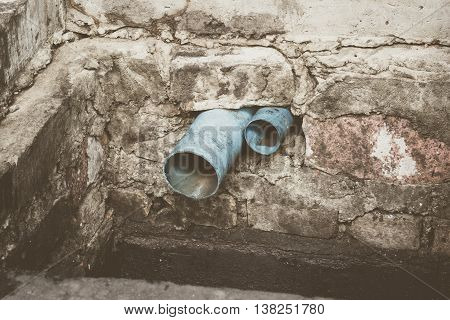 Blue PVC water pipe in dirty underground sewer for dredging drain tunnel cleaning selective focus (vintage effect)