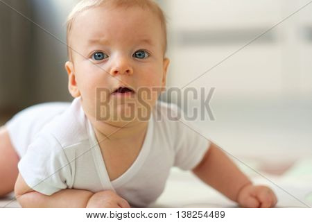 Four months old baby crawling on floor