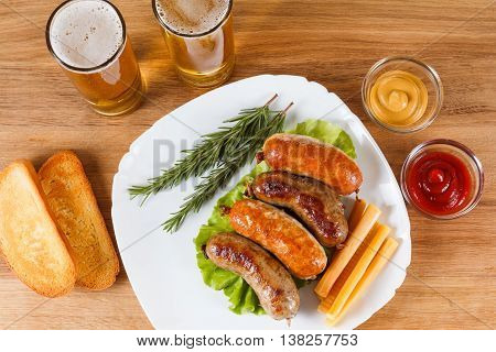 Oktoberfest traditional menu beer and roast beef or chicken sausage with ketchup mustard and rosemary. Wooden background