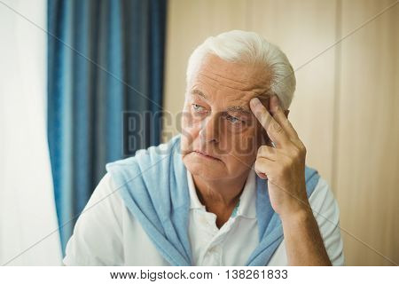 Sad senior man touching his head in a retirement home