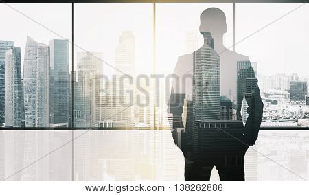 business and people concept - silhouette of businessman over office window and singapore city skyscrapers background and sun light double exposure effect