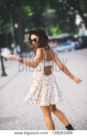 Back view of young beautiful girl in a summer dress dancing on street. Carefree hipster woman wearing hat and sunglasses feeling happy