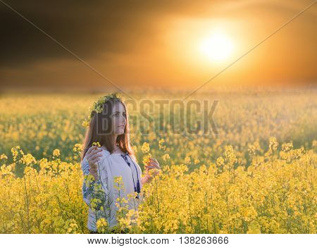 Portrait of a young woman in a rapeseed field. Young joyful girl wearing traditional romanian blouse