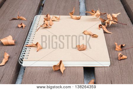 Closeup brown note book on wooden table in the garden with dried leaves textured background