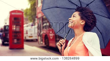 weather, travel, tourism, citylife and people concept - young smiling african american woman with umbrella over london city street background