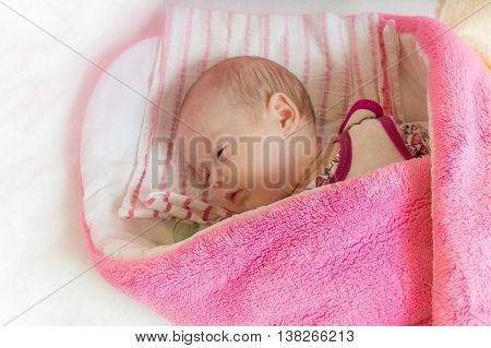 Swaddled Adorable Newborn Girl Is Sleeping In Bed.